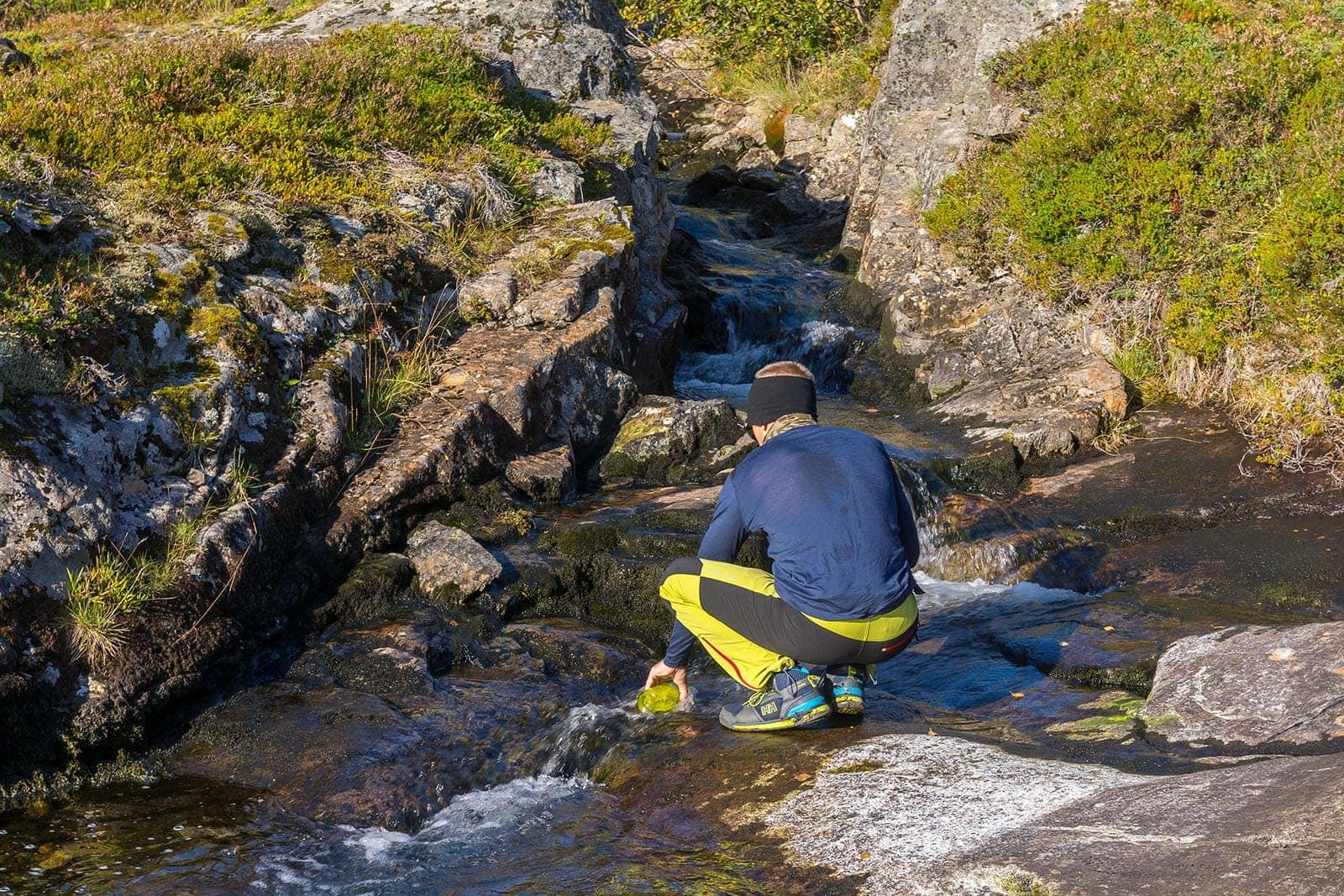 Mężczyzna, wędrowiec, nabierający wodę zestrumienia wgórach